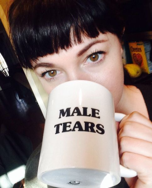 An attractive lady struggles to remove a 'male tears' mug from her face. Superglued rims are no joke :'(